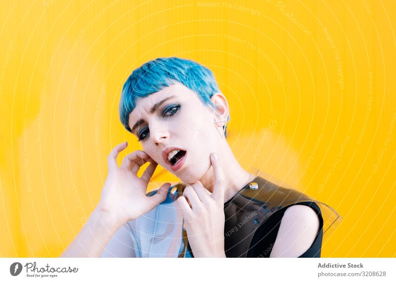Alternative model portrait against yellow wall woman futuristic alternative dress blue hair informal pavement glamour lady young expression vogue female beauty
