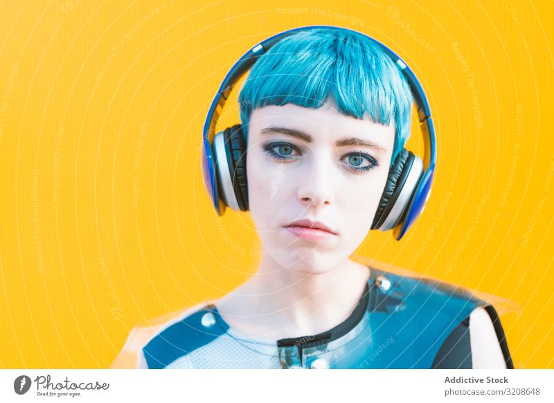Cool informal woman in headphones on street music smartphone generation cheerful expression vibrant urban listening futuristic subculture melody smiling