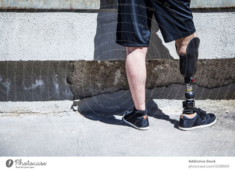 Unrecognizable young man amputated with his leg prosthesis expression disable male handicapped sit young adult amputation organ alone isolated disability care