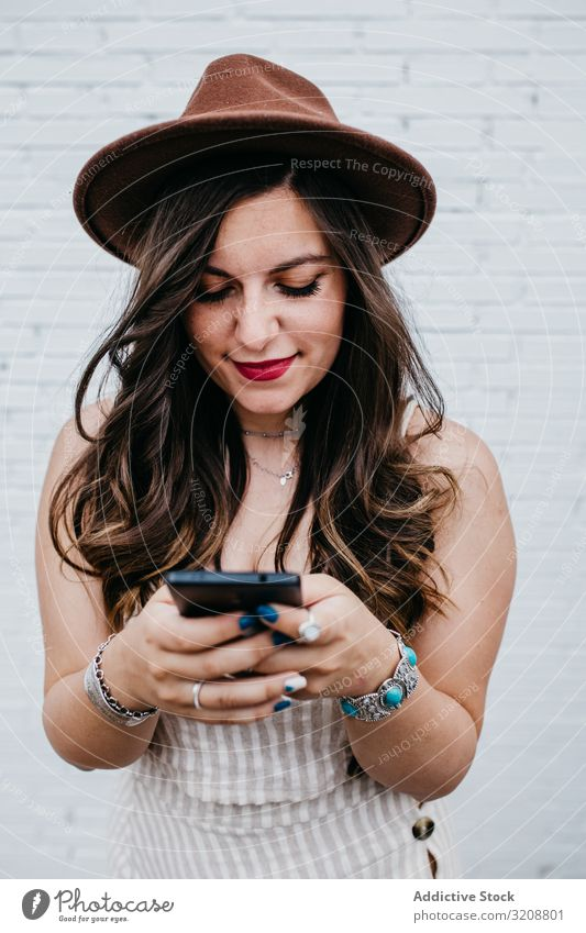 Woman in hat smiling browsing smartphone woman charming attractive young beautiful happy mobile phone using lifestyle casual boho texting female cheerful
