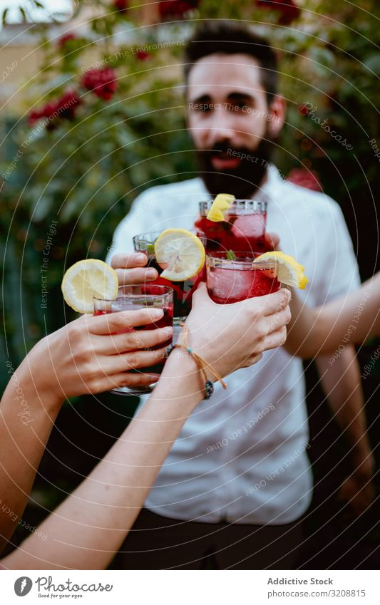 Group of cheerful friends clinking glasses at party yard colorful berry drink summer smiling cocktail hipster cheers friendship fun man happy people evening