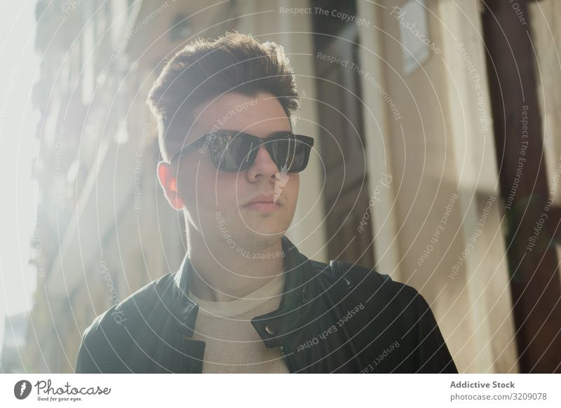 Smiling trendy man in sunglasses handsome sunlight summer freedom happiness street hairstyle leisure outside smile cheerful standing dreamer expression