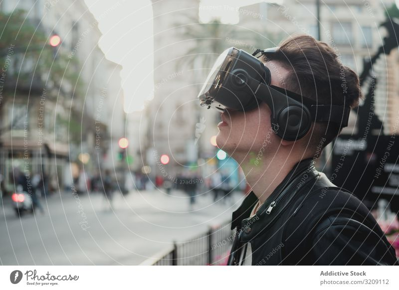 Young man wearing glasses of virtual reality on street vr urban millennial lifestyle technology cyber device imagination experience entertainment male enjoyment