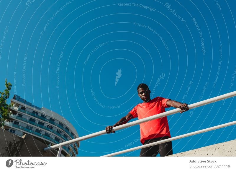 African American young man on bridge under blue sky urban sportive inspiration determined healthy muscular ethnic black african american geometric contemplate