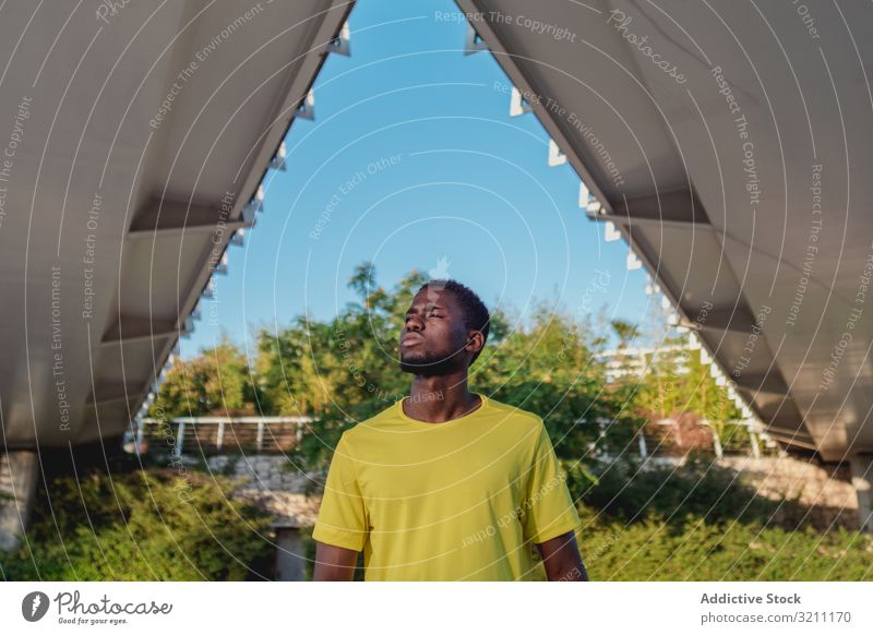 Strong black runner standing under bridge construction healthy strong architecture lifestyle workout ethnic african american summer athlete geometrical body