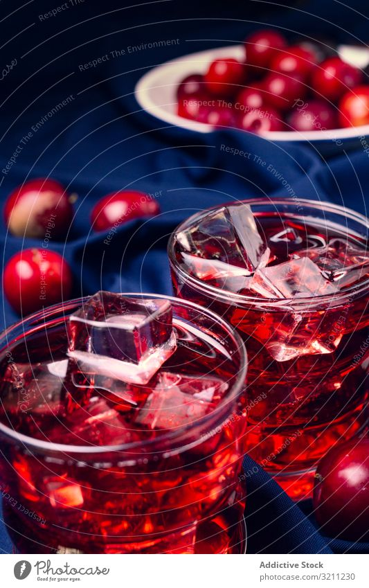 Red beverage near fresh fruits on cloth red glass fabric cold cocktail plum ice portion cubes drink summer refreshment juice food healthy alcohol cherry cool