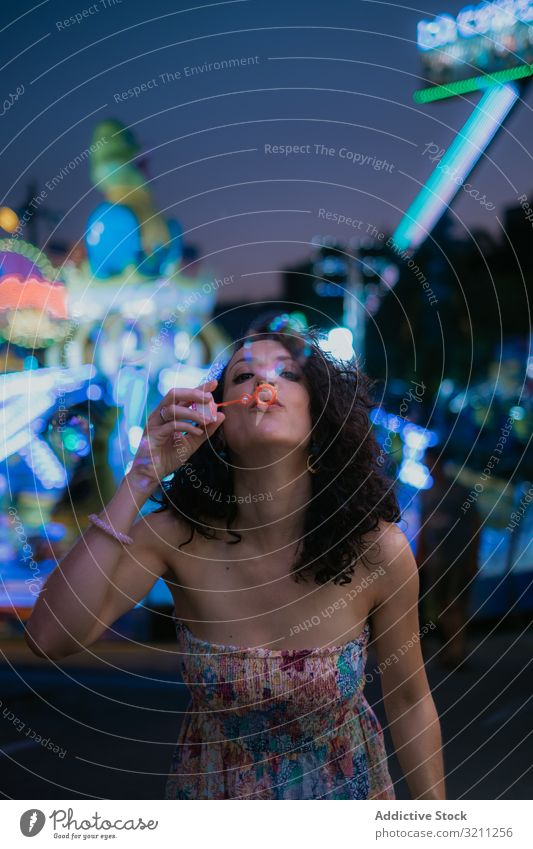 Woman in amusement park blowing bubbles woman summer fun leisure female brunette enjoy young evening beautiful holiday vacation attraction entertain sundress