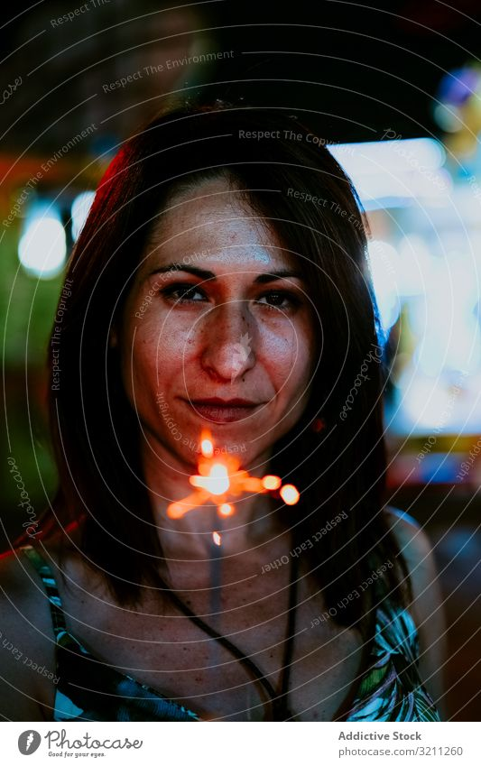 Woman holding sparkler on fairground in evening woman portrait summer vacation celebrate funfair smile young female brunette mysterious enjoy beautiful natural