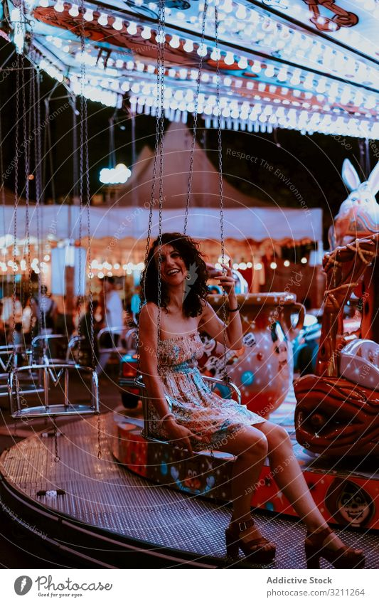 Woman enjoying ride on carousel woman amusement park summer cheerful evening fun leisure female brunette happy young beautiful holiday dress attraction