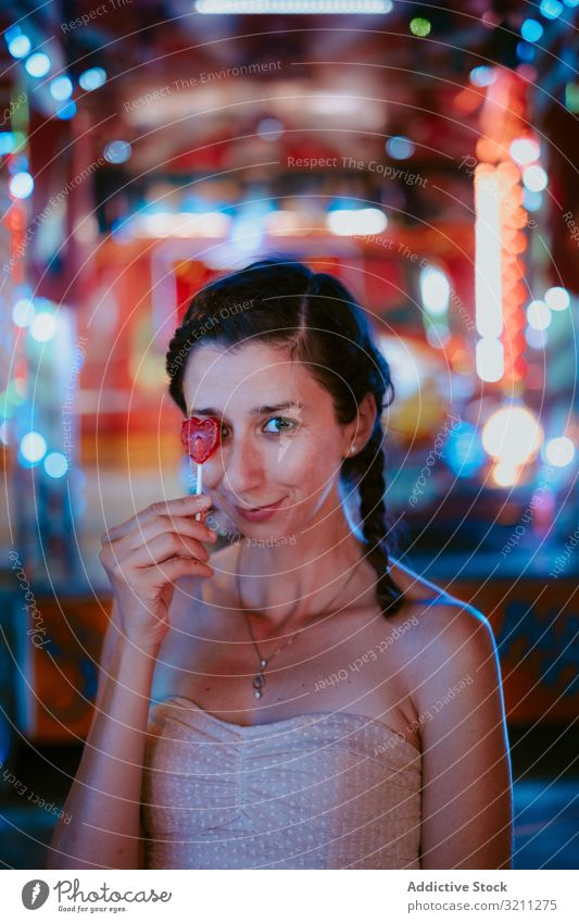 Woman with lollipop in amusement park woman funfair relax summer cheerful smile leisure female evening dark enjoy happy casual young beautiful holiday