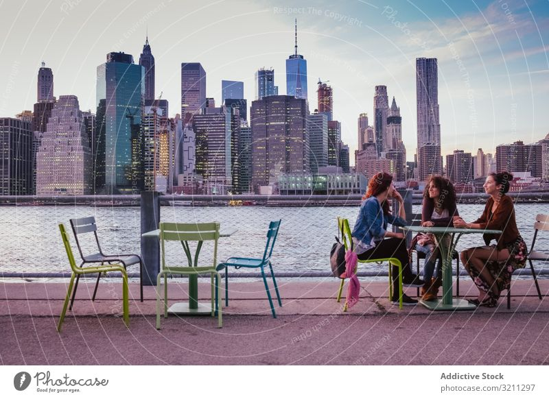 friends sitting on terrace with new york background at evening city view bridge river skyscraper architecture building cityscape travel modern urban landmark
