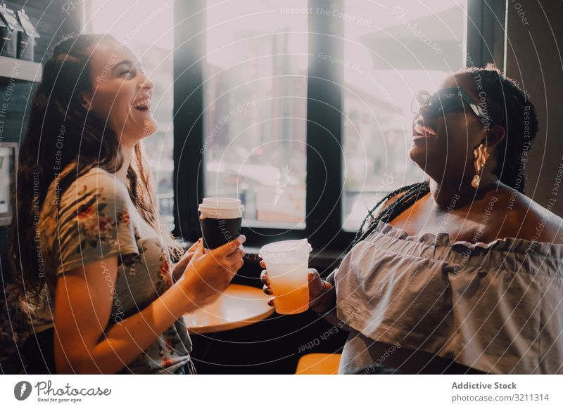 Multiethnic modern women relaxing at coffee shop laughing drink trendy sunset friend multiethnic multiracial african american black window cafe cup table