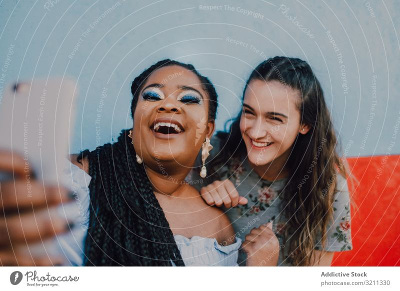 Smiling multiethnic women taking selfie smile laugh smartphone sit sofa modern trendy content attractive bright multiracial african american black happy casual