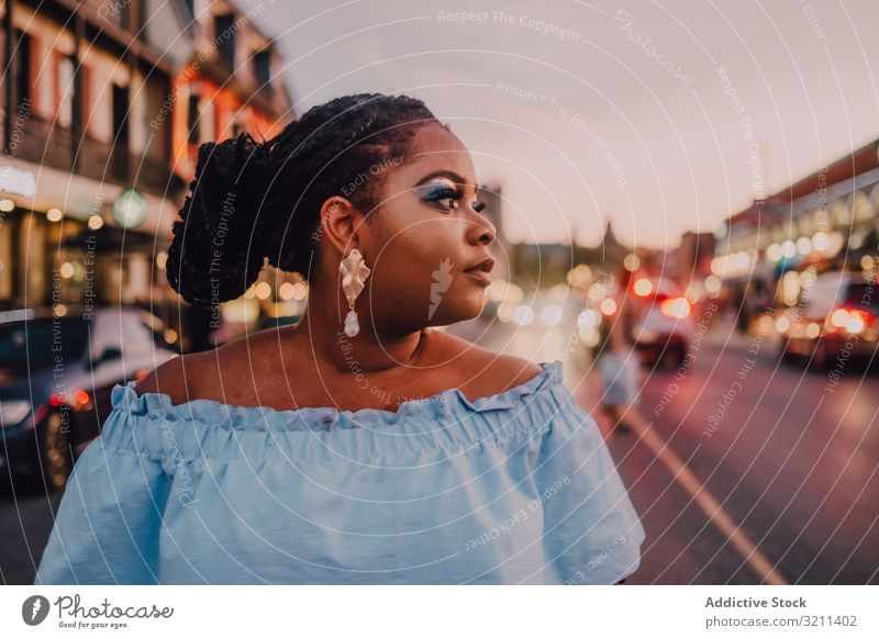Content trendy African American woman on street content attractive stand vibrant sunset african american black ethnic city dress long hair curvy plump modern