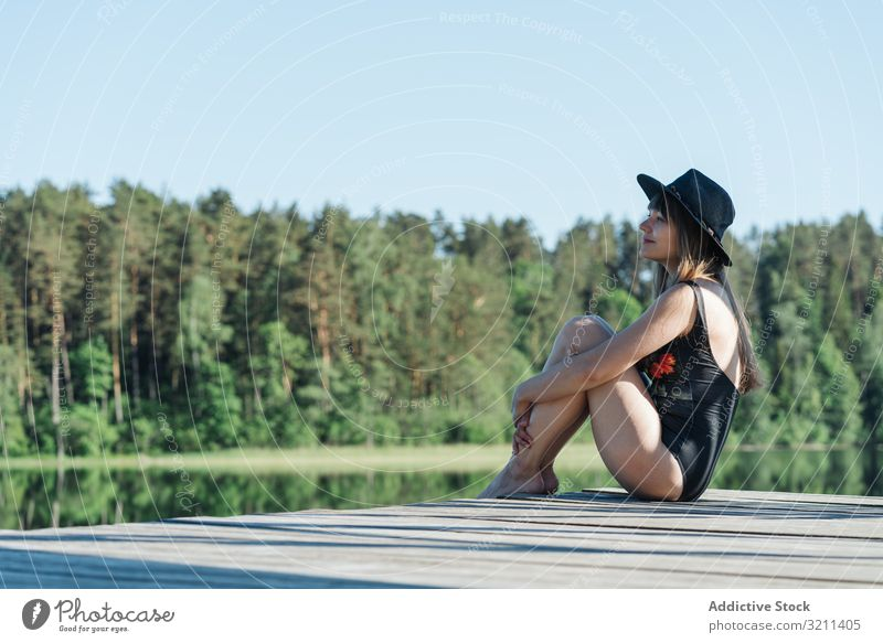Young female sitting on pier on nature woman admiring lake freedom travel tourism rest adventure forest tourist picturesque young happy joy rural scenic view