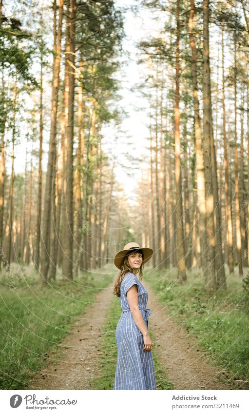 Young woman standing among pine trees forest road casual explore woods carefree walk straw hat sunny blond environment coniferous nida lithuania stroll dress