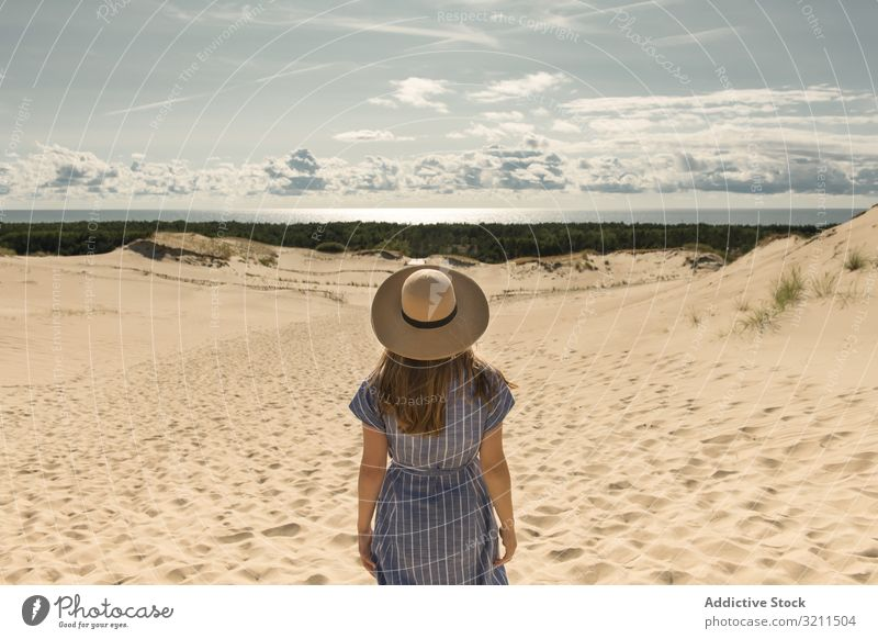 adult woman in casual dress and straw hat standing having good time on sand dune summer dreamy hot tourism modern clear sky scenic nida lithuania sunlight