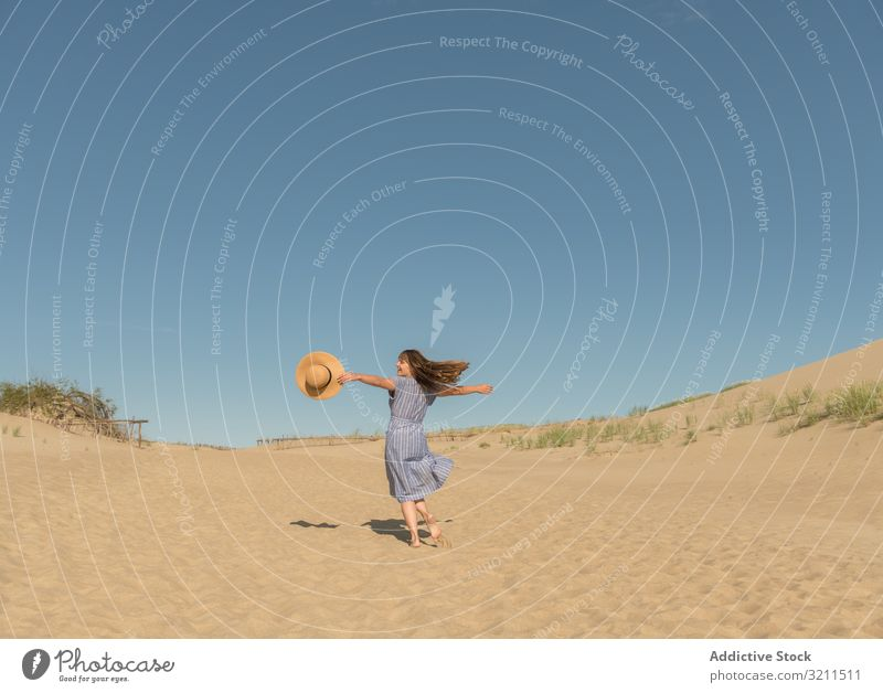 adult woman in casual dress and straw hat running having good time on sand dune summer dreamy hot tourism modern clear sky scenic nida lithuania sunlight sunhat