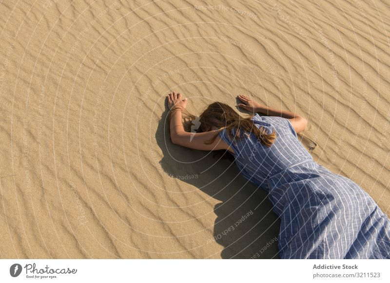 Young woman lying down on sand dune desert tired hot face down thirst exhausted sunlight casual drought summer dress freedom nida lithuania grass cloud