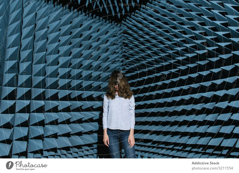 Woman in middle of sound room shaking head woman music enjoy covering face modern beautiful entertainment contemporary unusual soundproof standing young female