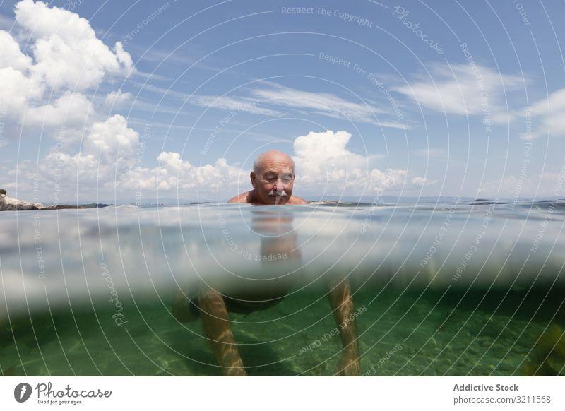 Cheerful elderly man swimming in sea water vacation senior crystal retired travel leisure greece halkidiki ocean mature happy floating nautical summer enjoy