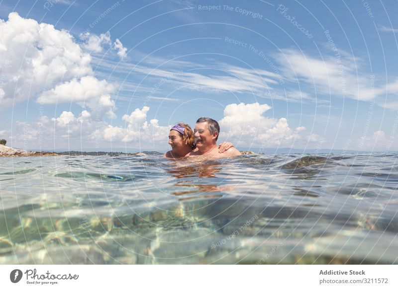 Mature couple swimming together in fresh water vacation crystal sea ocean retired greece halkidiki floating sunny holiday nautical relaxing wave summer elderly