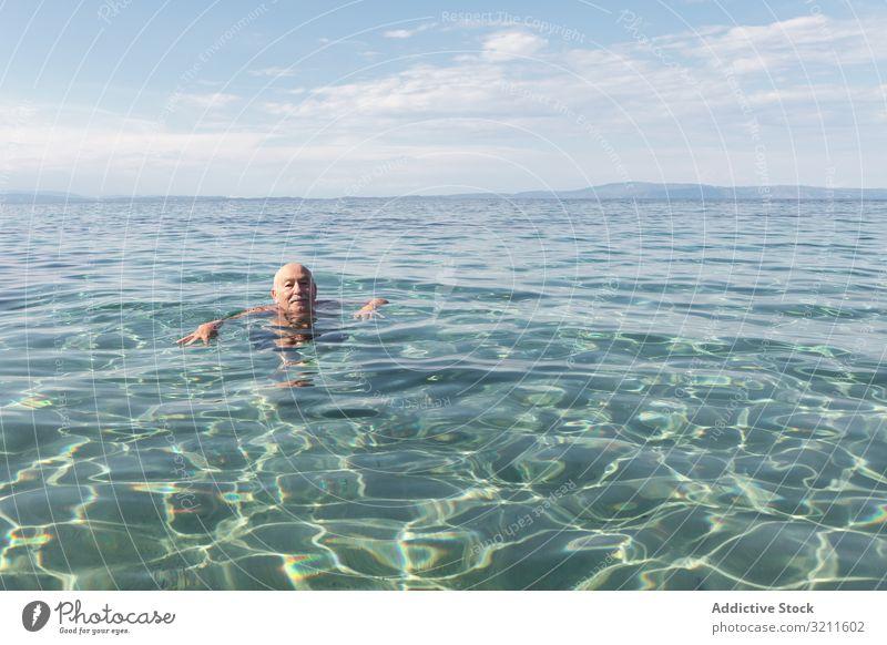Mustached elderly man swimming in clear water sea retired vacation senior greece halkidiki ocean marine crystal leisure happy floating energy seashore summer