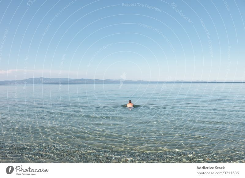 Man swimming in clear water in sunlight man sea ocean vacation summer travel greece halkidiki adventure lifestyle calm activity trip tranquil serene athlete