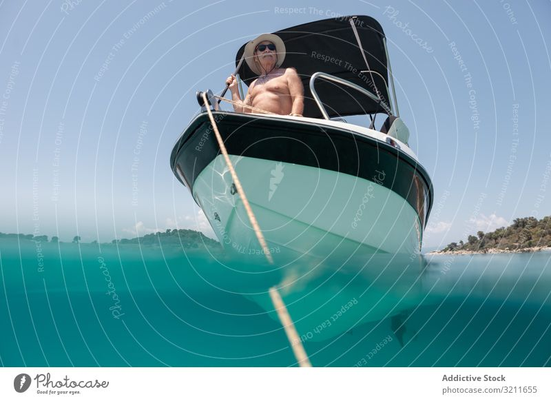 Man sailing in boat in clear turquoise water man yacht elderly vacation summer nautical travel sea luxury leisure halkidiki sailor greece freedom traveler