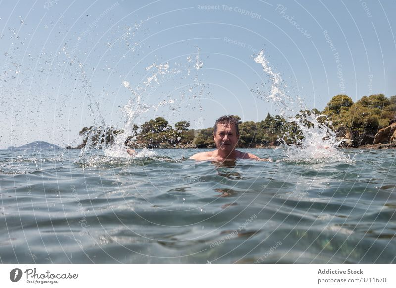 Active senior man swimming and splashing in water elderly retired travel mustache vacation halkidiki greece athlete sunlight sea ocean marine nautical summer