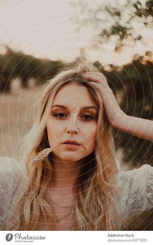 Thoughtful beautiful woman with flowing hair and straw in mouth bride boho lace dream style tender sensual natural summer romantic wedding olive tree blonde