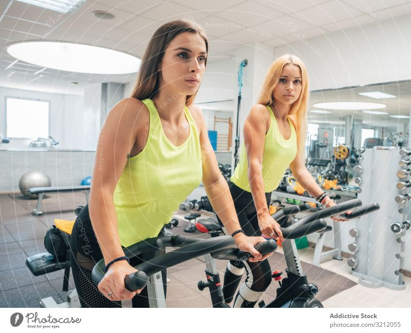 Young women exercising on machines together cardio gym spinning cycling bicycle modern athlete exercise workout sport team warm up power training female young