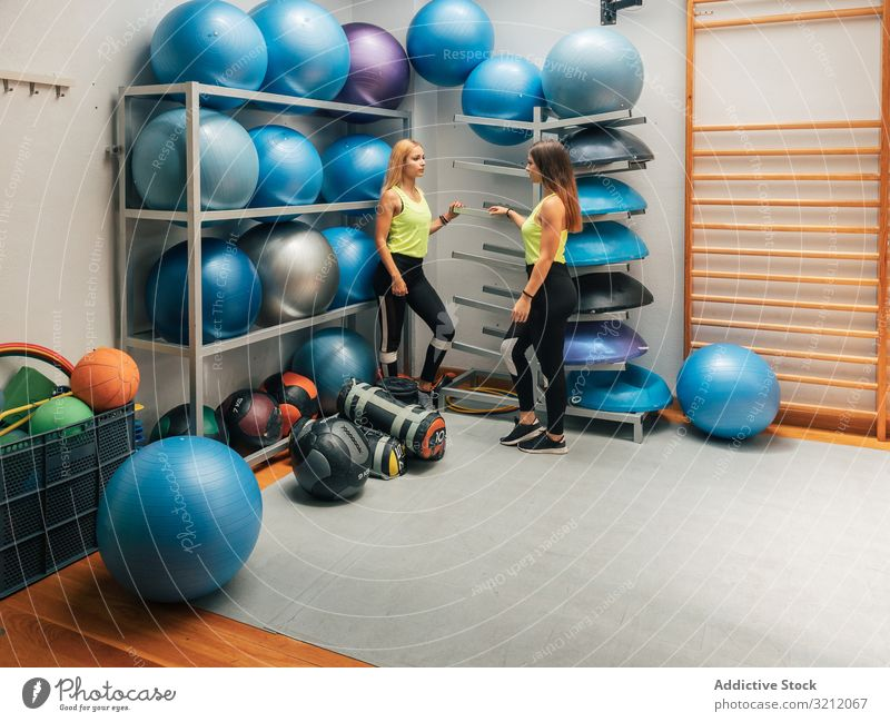 Sportswomen standing near equipment rack in gym sportswomen modern break workout center team club ball class motivation strength sportswear wellness interior