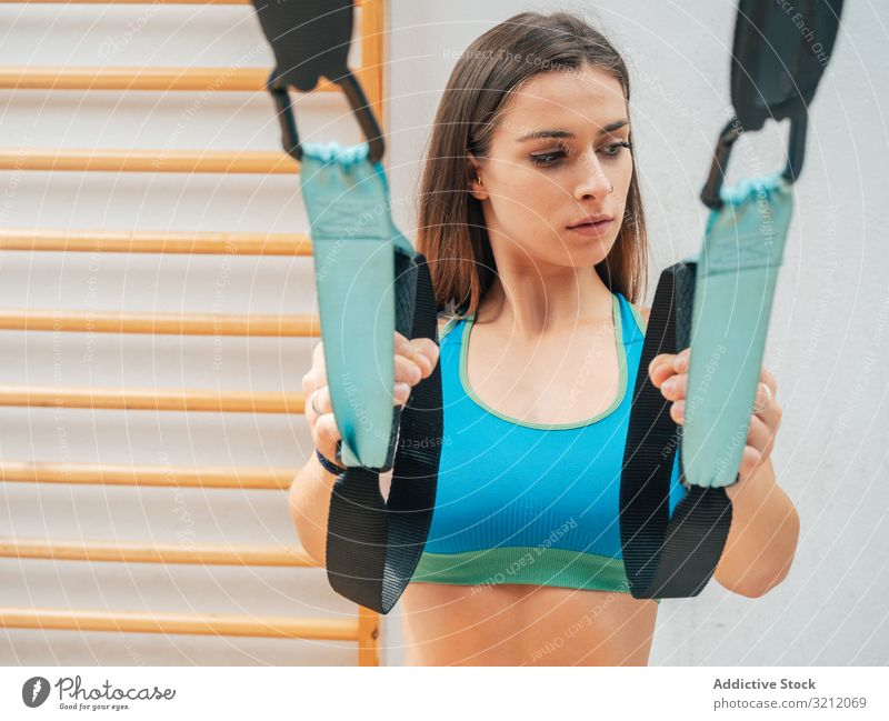 Young female training at the gym sportswoman suspension rope exercise trx bodyweight hanging physical athlete workout motivation strength power modern wellbeing