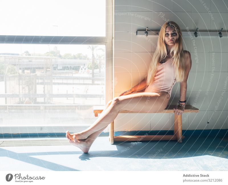 Young woman in dressing room of swimming pool swimwear fitness sensual bench sit young sunlight sportive female window barefoot gym slim swimsuit harmony