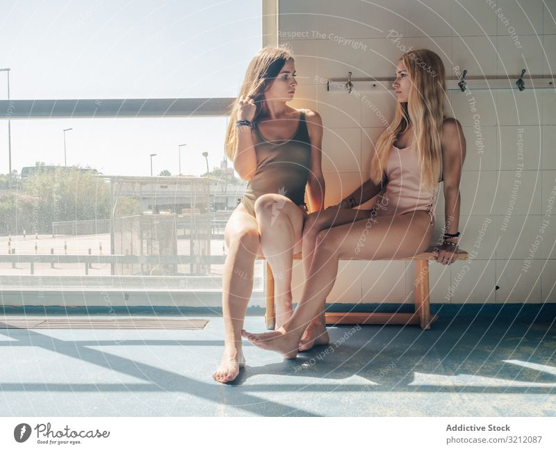 Young women in dressing room of swimming pool swimwear fitness sensual bench together friend tender sit young sunlight sportive female window barefoot gym slim