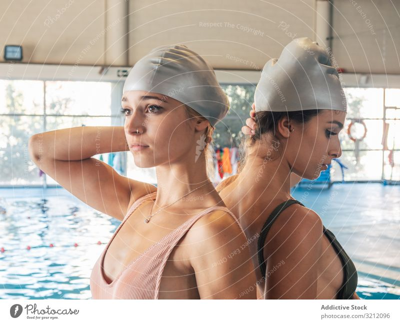 Slim ladies wearing swimming caps in pool women young team water gym female friend facility back to back protection partner together leisure lifestyle swimwear