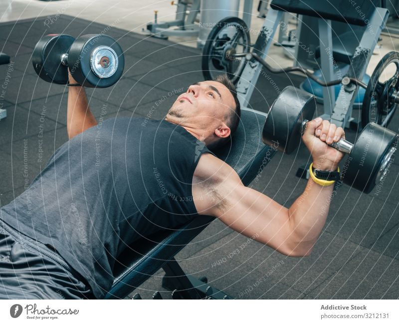 Strong man exercising with dumbbells on bench athlete lying lift press exercise bodybuilding gym focused motivation endurance male workout sport strength power
