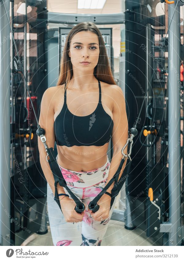 Slim woman exercising on resistance trainer athlete exercise rope chest fly gym sportswear determined workout motivation strong power modern effort training