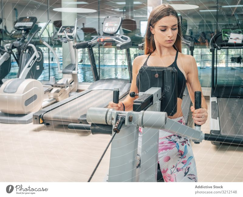 Strong female on row machine exercise gym workout sport athlete woman strength power back modern training fit young fitness healthy wellness wellbeing vitality