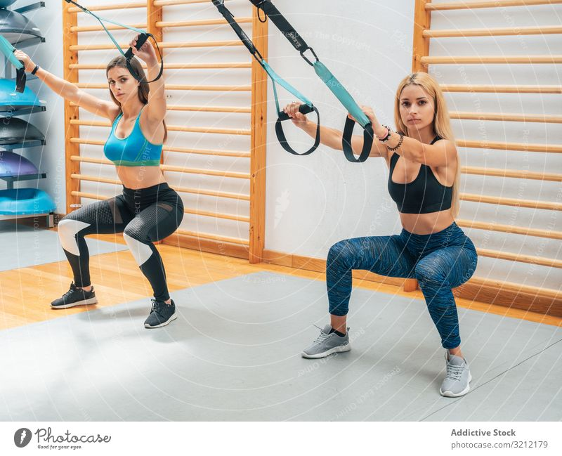 Strong ladies squatting with ropes sportswomen training suspension fitness athlete exercise trx wellbeing determination equipment sportswear gym workout