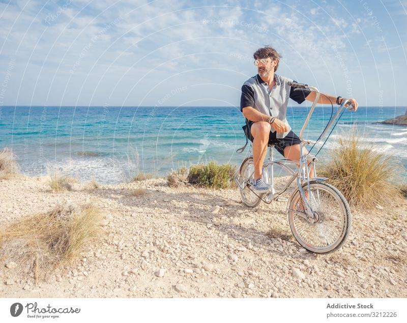 Man cycling on sandy beach hill man bike seaside vacation happy summer wave active lifestyle holiday trip energetic travel journey male offroad terrain freedom