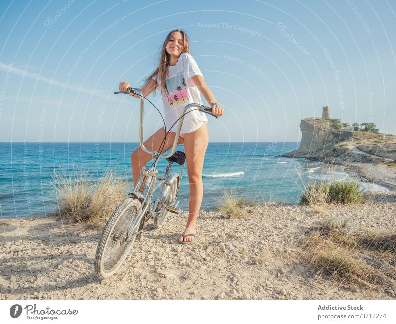 Woman cycling on sandy beach hill woman bike seaside vacation happy summer wave active lifestyle holiday trip energetic travel journey young female offroad