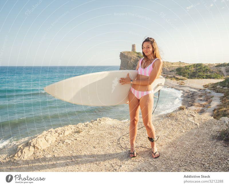 Woman raising surfboard high staying on seashore woman beach swimsuit car tanned seaside vacation slim sunbath active sport lifestyle summer attractive female