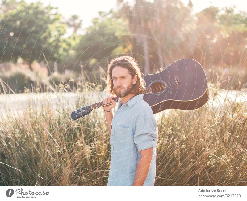 Hipster man in jungle with guitar hipster musician playing adventure trip summer lifestyle pensive male acoustic young entertainment leisure practice nature