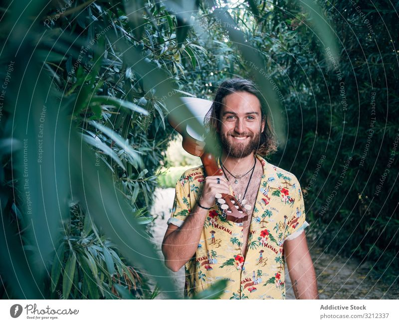 Hipster man in jungle with ukulele hipster musician travel adventure trip summer lifestyle pensive male vacation freedom young tourist colorful casual tropical