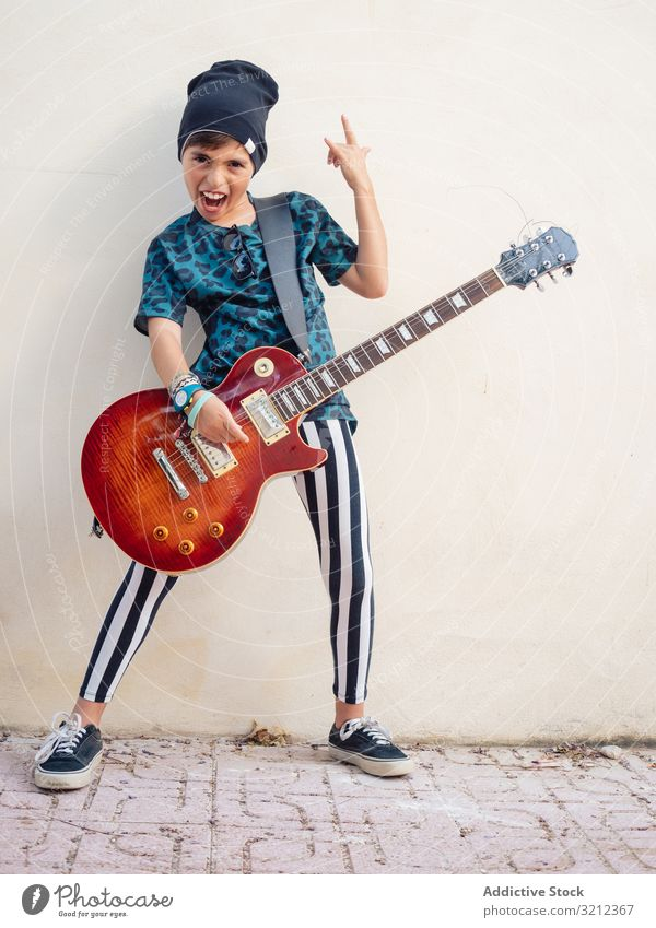 Energetic kid gesturing rock holding guitar boy playing rockstar colorful childhood fashion sign gesture artist musician festive laugh little contemporary funny