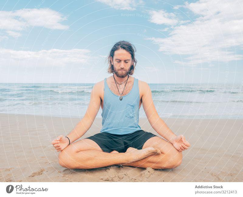 Man training yoga on beach man rest harmony asana exercise seashore energy meditation equilibrium stretch zen relax balance sport lifestyle calm male bearded