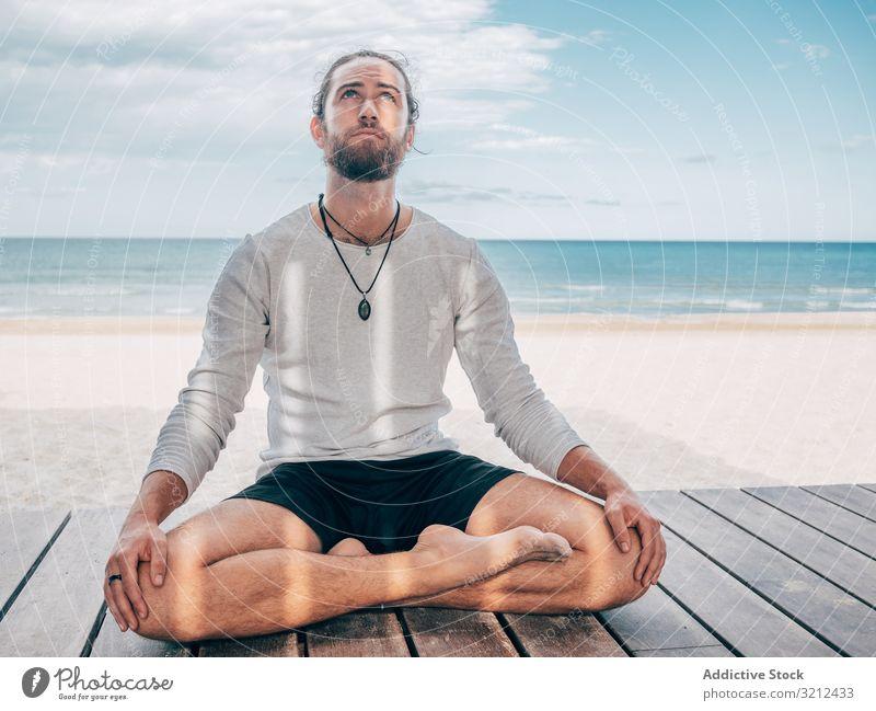 Man meditating on beach man meditate rest calm lotus position resort brutal harmony relax summer beard practice yoga hobby asana sport vacation active sitting