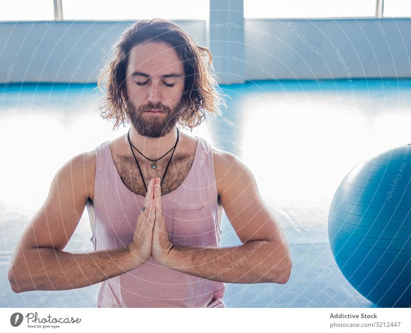 Male meditating in spacious room man meditate gym lotus relax yoga vitality zen harmony fitness exercise asana sport legs crossed young calm peace male bearded